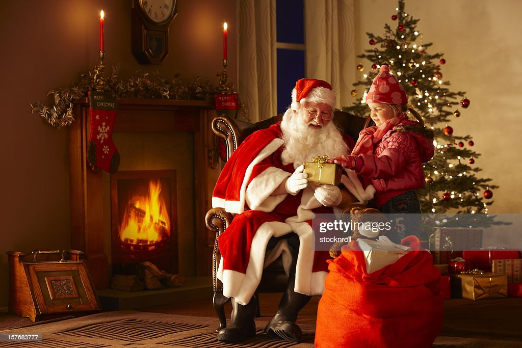 Little girl giving gift to Father Christmas in grotto : Stock Photo