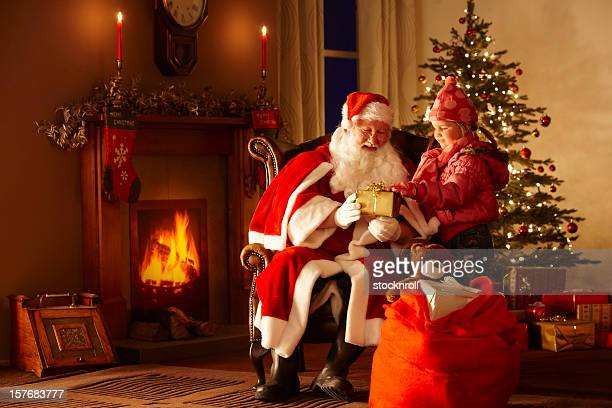 little girl giving gift to father christmas in grotto - santa stock photos and pictures