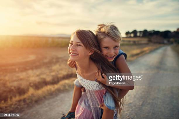 little girl giving her brother a piggyback ride - sister stock pictures, royalty-free photos & images