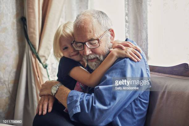 little girl giving her grandfather a hug - aanhankelijk stockfoto's en -beelden