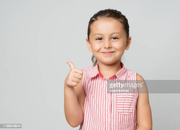 little girl giving thumbs up - bambine femmine foto e immagini stock
