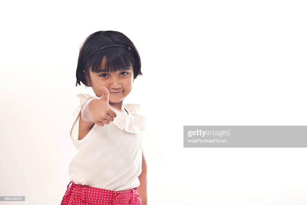 Little girl giving thumbs up : Stock Photo