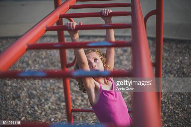Little girl Going Swinging Across Monkey Bars