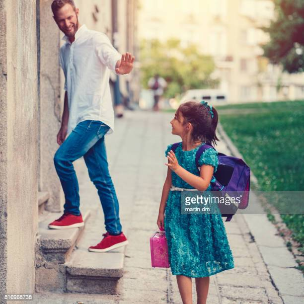 Kleines Mädchen zur Schule zu gehen und winkte mit der Hand ihres Vaters