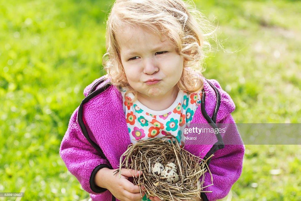 Rapariga Fazer Caretas e segurar Ninho com Ovos : Foto de stock