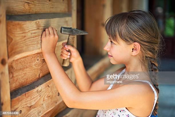 Little girl hammering a nail