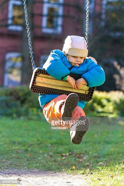 Little girl hanging on a swing