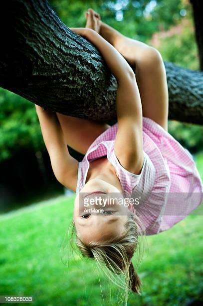 Kleines Mädchen hängen auf einem Baum branch