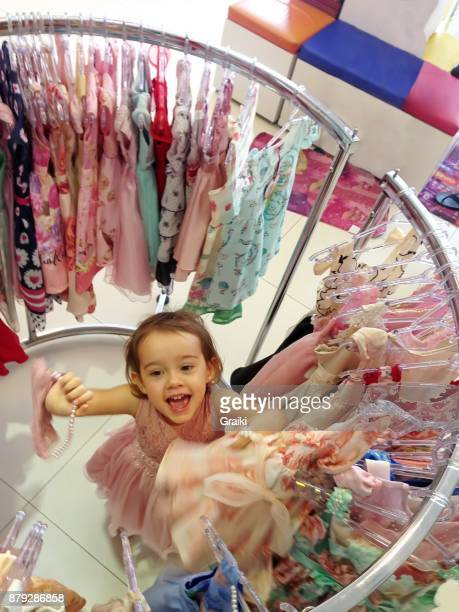 Little girl happy to buy a dress in the store