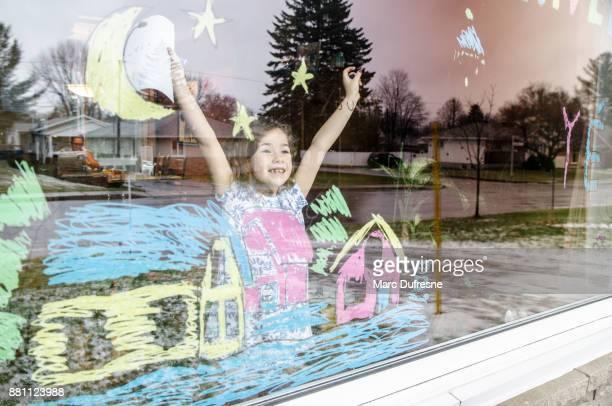 Petite fille heureuse d'avoir completer son dessin coloré sur la fenêtre du salon: une ambiance d'hiver pour être vu de l'extérieur