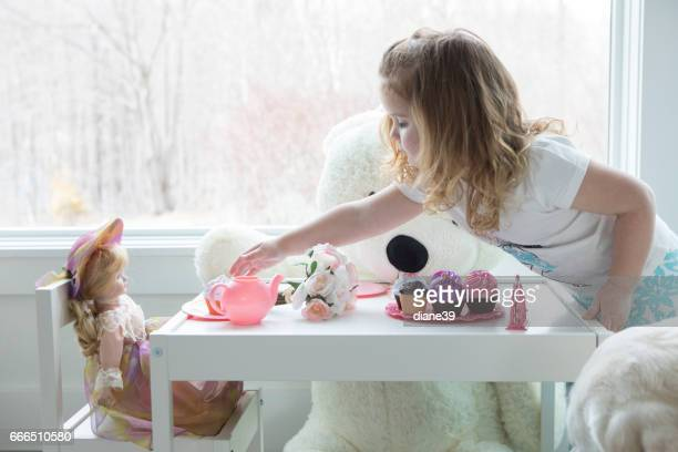 A little girl having a tea party
