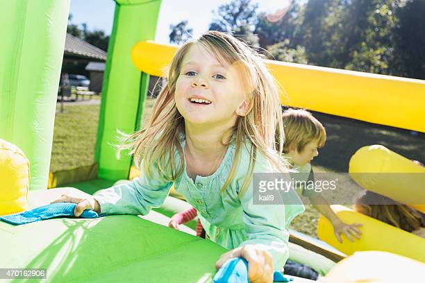 little girl having fun climbing on a bounce house - fun house stock pictures, royalty-free photos & images