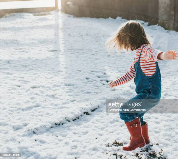little girl having fun in a light dusting of snow - she wears bright red wellington boots - snow boot stock pictures, royalty-free photos & images