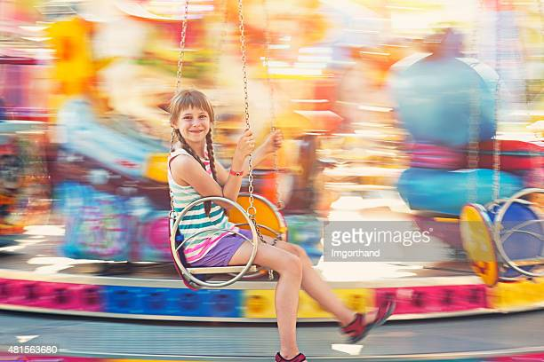 Little girl having fun on swing carousel.