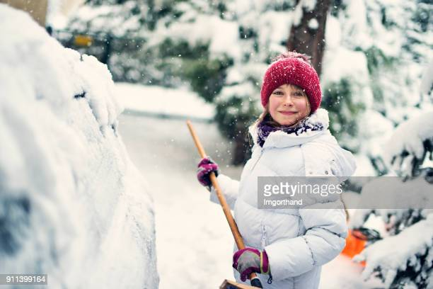 little girl having fun removing snow from car with broom - thick girls stock photos and pictures