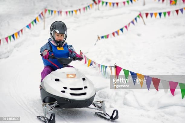 Little girl having fun riding snow scooter