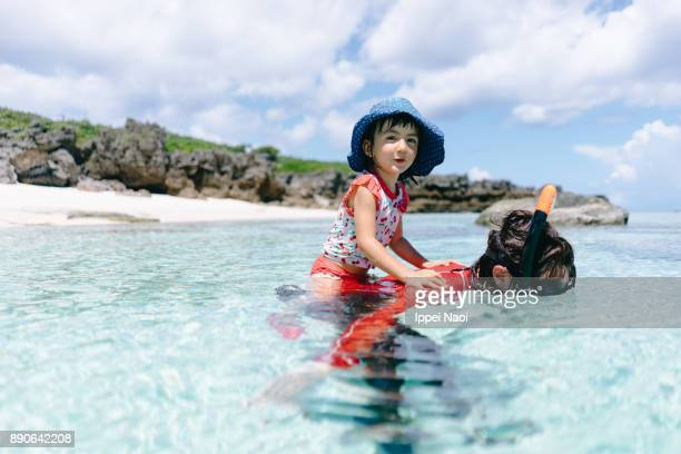 Little girl having fun with mother in tropical water, Amami Islands, Japan