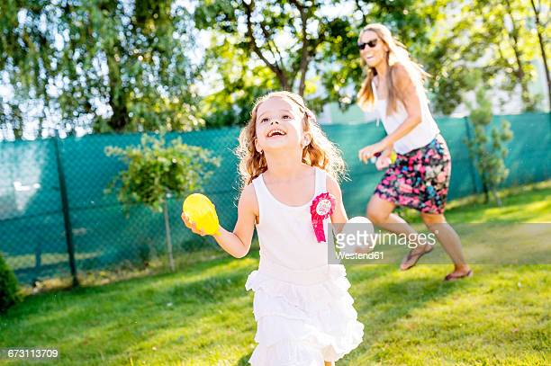 Little girl having fun with water bombs in the garden