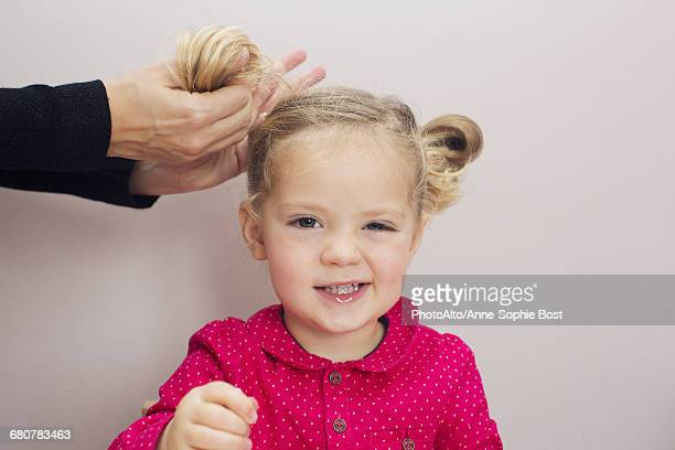 little girl having her hair arranged in pigtails - anne sophie mutter stock-fotos und bilder