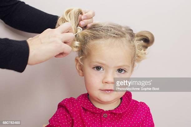 Little girl having her hair arranged in pigtails