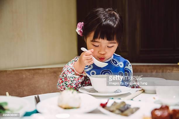 Little girl having hot soup herself in restaurant