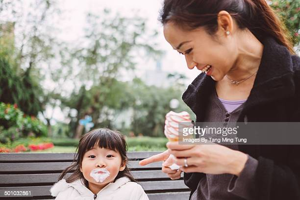 Little girl having ice cream cone with mom in park