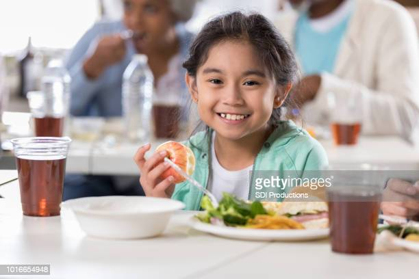 Little girl having lunch in soup kitchen
