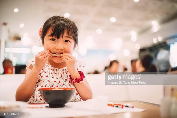 Little girl having meal in restaurant