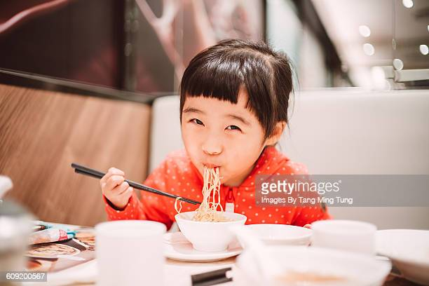 Little girl having meal in restaurant