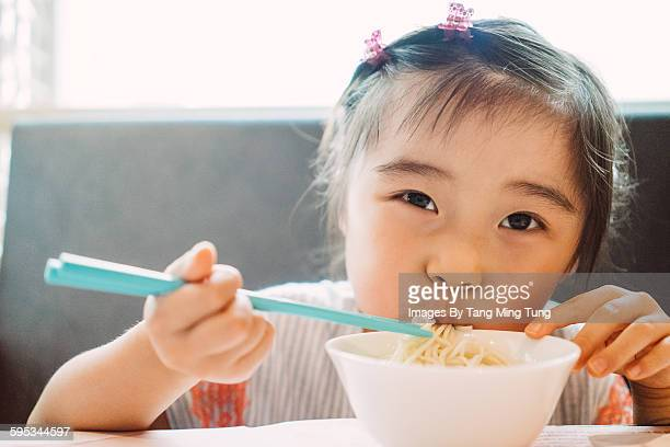 Little girl having noodle with chopsticks