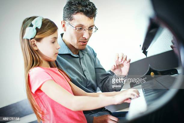 Little girl having piano class with her teacher.