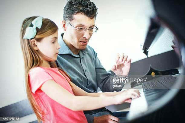 Petite fille avec classe avec son professeur de piano.