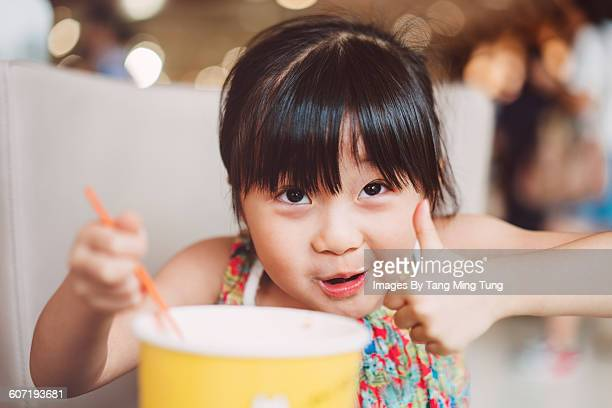 Little girl having snack joyfully in cafe