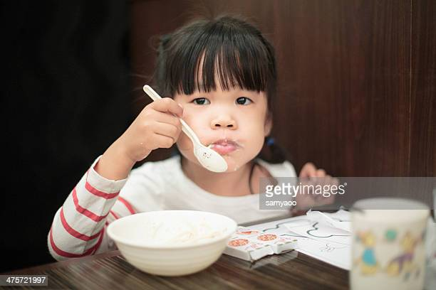 Little girl having soap with spoon