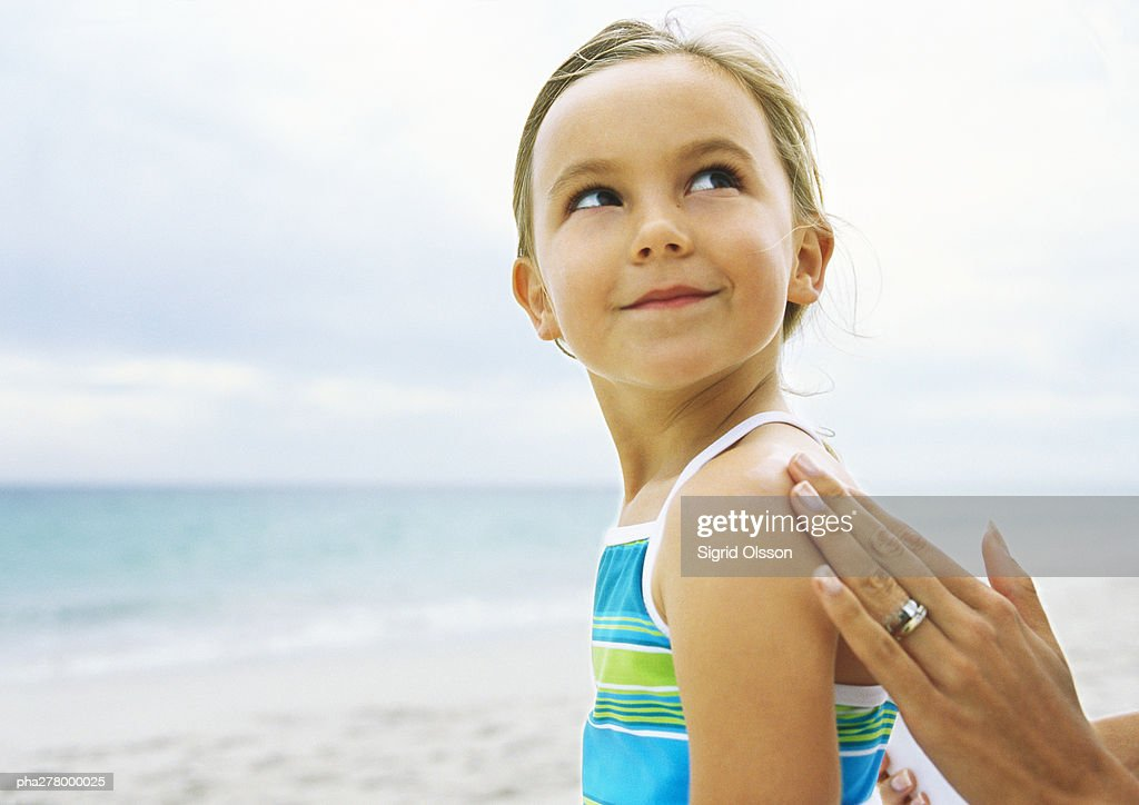 Little girl having sunscreen rubbed into shoulder : Stockfoto