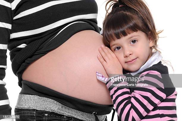Little girl hears the mother's belly