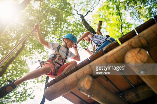 little girl helping her brother on ropes course - doing a favor stock pictures, royalty-free photos & images