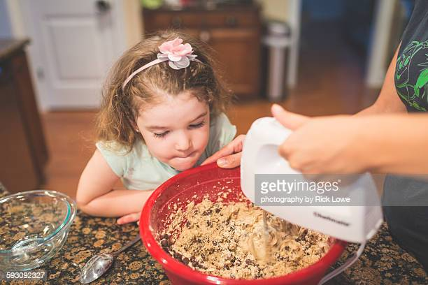Little girl helping her mother cook