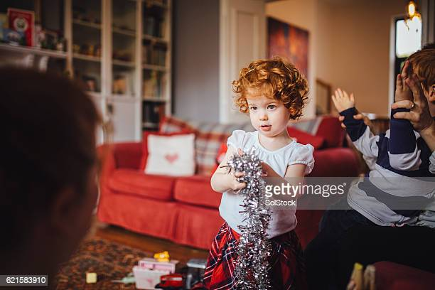 little girl helping her mother with the christmas decorations - tinsel stock pictures, royalty-free photos & images