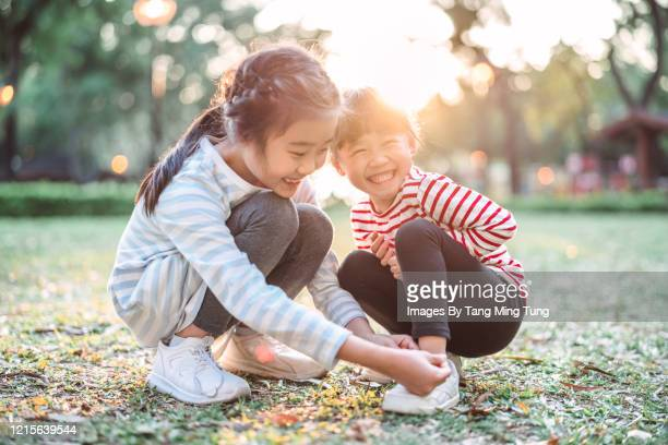 little girl helping her sister to tide her shoelace in park - east asian ethnicity stock pictures, royalty-free photos & images