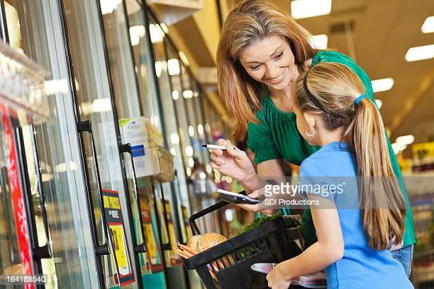 Kleines Mädchen helfen Mutter Einkaufen im Supermarkt mit Einkaufsliste