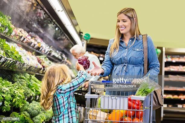 Little girl helping mom shop for vegetables in supermarket