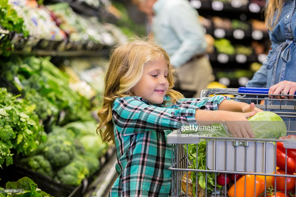 Little girl helping mother shop for produce in grocery store : Stock Photo