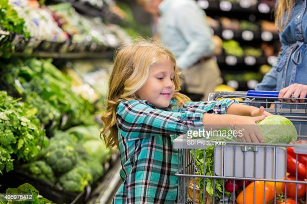 Little girl helping mother shop for produce in grocery store