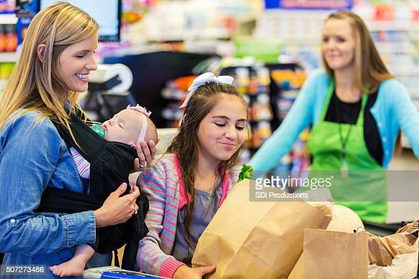 小さな女の子サポートし、ショッピングバッグマザーにチェックアウトカウンター