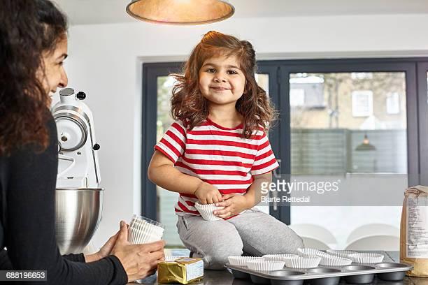 Little girl helping mum making cupcakes