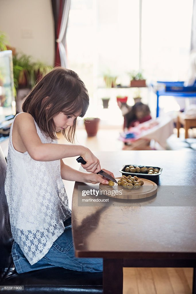 Little girl helping preparing meal on kitchen table at home. : Stock Photo