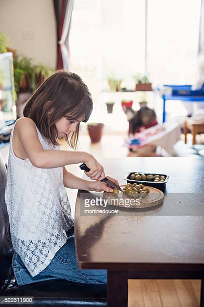 "little girl helping preparing meal on kitchen table at home. - ""martine doucet"" or martinedoucet stockfoto's en -beelden"
