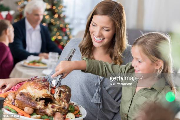 Little girl helps her mom serve Christmas turkey