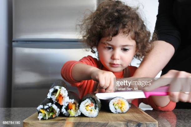 little girl helps her mother to cut sushi - rafael ben ari stockfoto's en -beelden